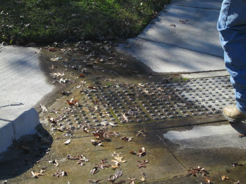 The curb ramp shows water accumulated